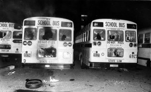- -Text: Violence and protests erupted with the onset of busing. - -School buses damaged by protesters stand in the parking lot at Southern High School