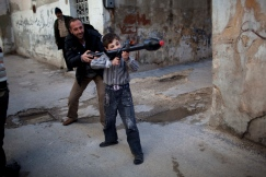 A man teaches Bilal, 11, how to use a toy rocket propelled grenade in Idlib, northern Syria, March 4, 2012. Photo by Rodrigo Abd