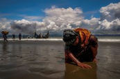 An exhausted Rohingya refugee woman touches the shore after crossing the Bangladesh-Myanmar border by boat through the Bay of Bengal, in Shah Porir Dwip, Bangladesh September 11, 2017. REUTERS/Danish Siddiqui TO FIND ALL PICTURES SEARCH REUTERS PULITZER